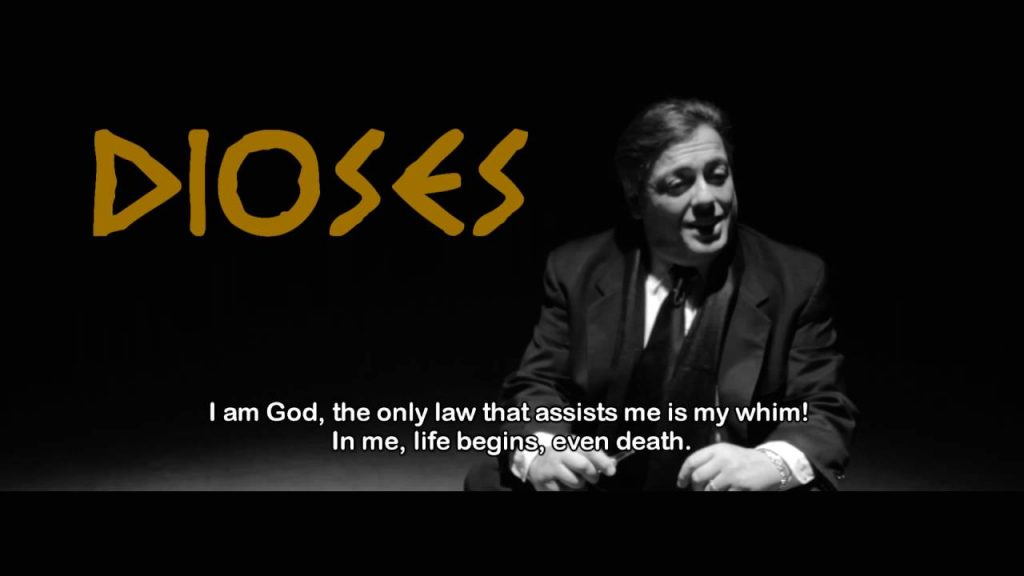 """[Thumbnail image of trailer video, showing title """"Dioses"""", with an image of Martin de Leon as God in black and white, sitting on the floor with a mocking expression. The subtitle reads: """"I am God, the only law that assists me is my whim! In me, life begins, even death.""""]"""
